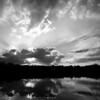 Prairie Oaks sunset in June with reflections in the still water of the quarry lake done in monochrome.   Photographed at Prairie Oaks Metro Park outside Galloway, Ohio.