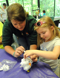 Delaney Corso, 6, of Amherst, makes a snowy owl ornament from a pine cone with help from Lorain County Metro Parks naturalist Rachel Mazzola, at Branching Out Camp at French Creek Nature Center in Sheffield on Tuesday, June 7. STEVE MANHEIM/CHRONICLE