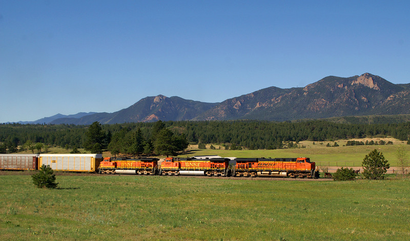 Railroad traffic is starting to pick up in Colorado. A northbound auto train rolls through Monument in the background is Mount Herman.