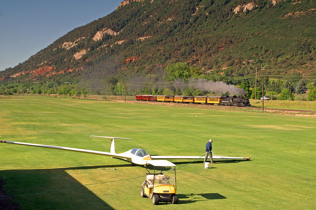 At the Hermosa glider port they ready the plane for its next departure, while in the background the first of three Durango to Silverton passenger trains polishes the steel rails through the Hermosa Valley north of Durango, CO