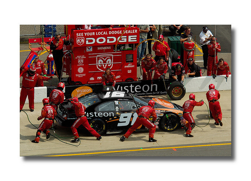 What makes this shot interesting is the fact that it never happened....  The agency wanted a pit road action shot of the Visteon car, the problem was I was not able to get the shot at the brickyard race when the car ran.  So I went to the MIS race and shot another team members car the Dodge/Moutain Dew crew RED #19.  Then I retouched in, using photoshop, the whole image changing the car by adding a new skin, changing their uniforms, helmets, shoes, knee protection, wheels, crew chief stand, adding a banner on the wall so many things to come up with the shot.