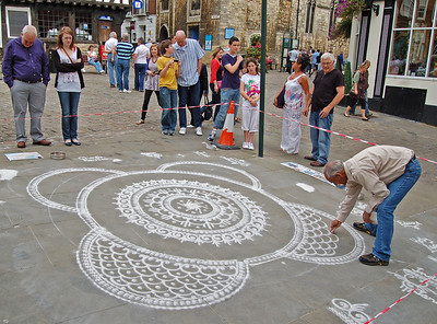 This guy isn't drawing with chalk, he's pouring marble powder through his fingers to make the patterns. It is an Indian art form called Rangoli  The artist is Janak Chauhan