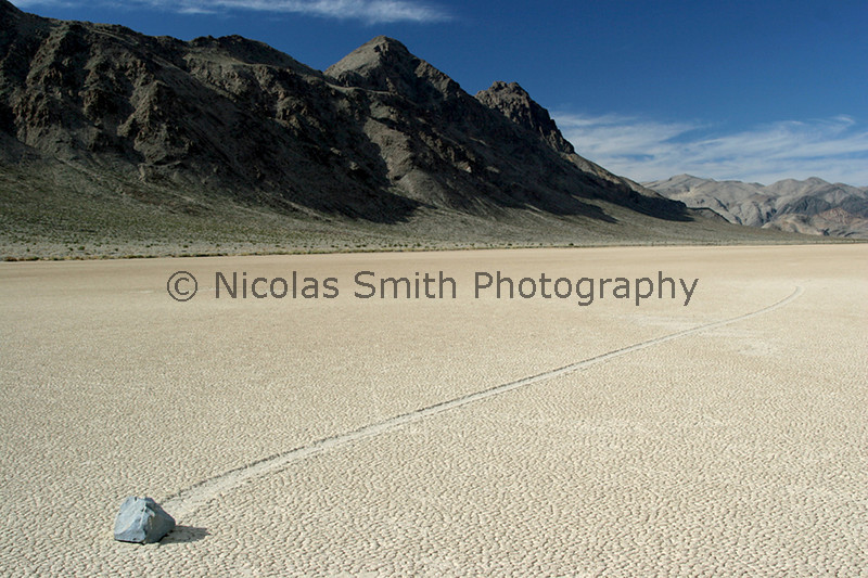 Moving Rocks: Racetrack, Death Valley, 2005;  Yes, these rocks do move, and without human intervention.  When the rare rains fall in this remote area of Death Valley, the clay becomes very slippery.  Strong winds will then push these massive rocks along the lake bed--leaving behind a scar that hardens as the desert sun dries the Racetrack again.  *All images and gift items print without the watermark*