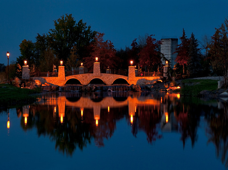 This stone bridge at night is lit by small latterns