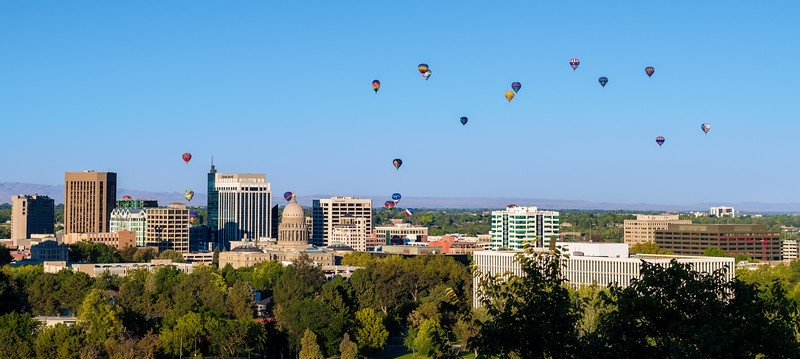 Hot air balloons fly over the city of Boise with a glimpse of St. Als