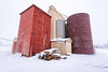 Winter snow storm and old painted grain elevators