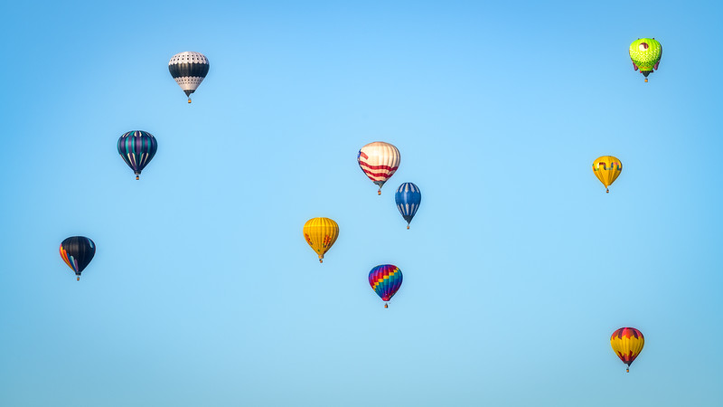 Balloons float through the sky in small groups with blue sky