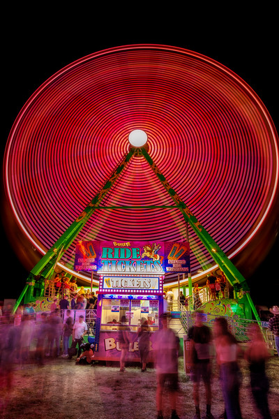 Ferris wheel spins with people in line at the ticket booth