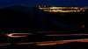 Car light streak down Bogus Basin in winter with city lights