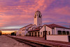 Train tracks lead past the Boise train depot at sunset