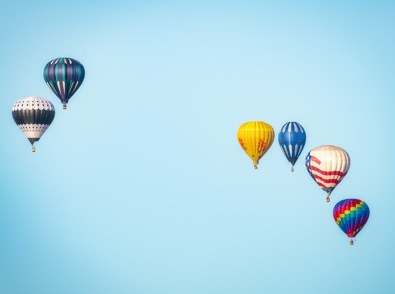 Six colorful hot air balloons in two small groups against a blue sky
