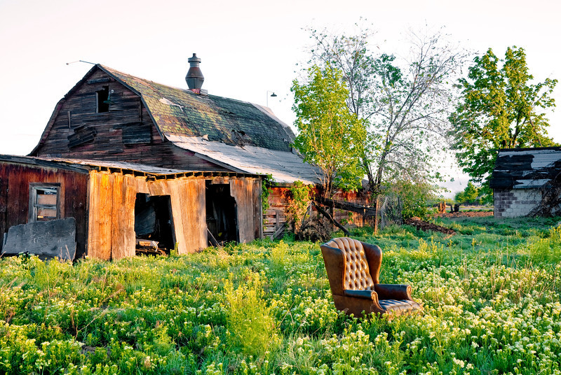 Field with a barn and an abandoned chair