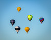 Hot air balloons flot above the earth