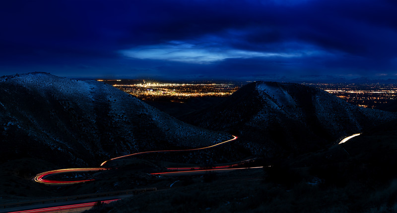 Car light streak down Bogus Basin in winter with city lights