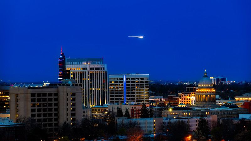 Airplane lights fly over the Boise skyline at night
