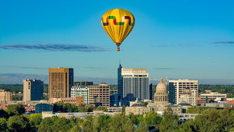 Single yellow hot air balloon over the city of Boise Idaho