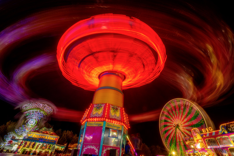 Spinning ride at the fair in the late night illuminated with lights