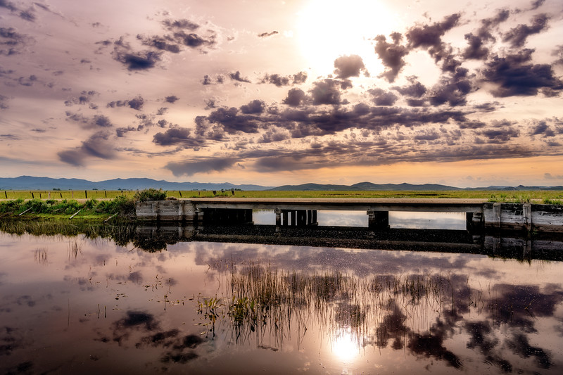Rural country bridge with clouds and sun reflections
