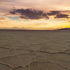Spectator watches the sun set over the salt flats in Utah with car tracks in the salt