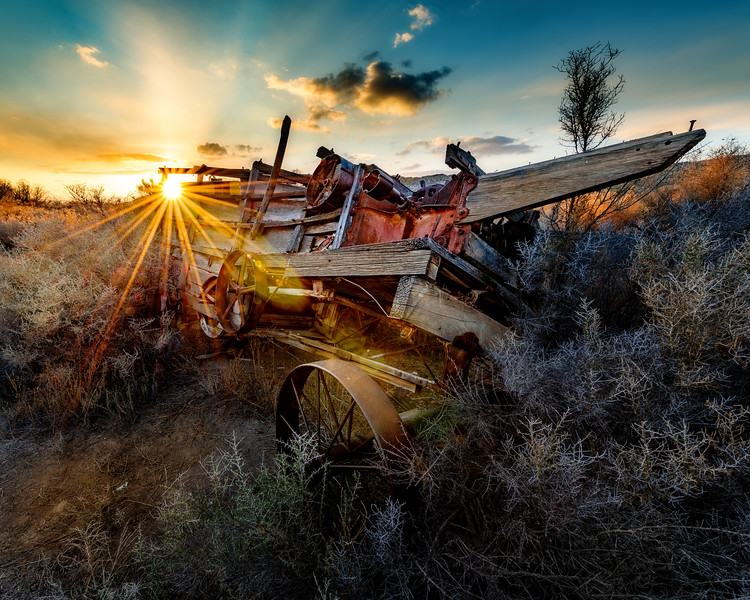 Uncovered wagon at sunset with a sunburst shining through