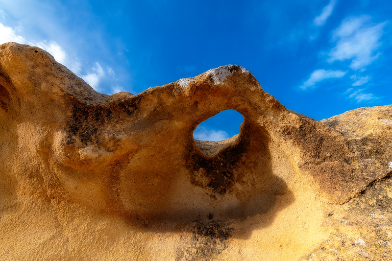 Looking to a deep blue sky through whole formed in rock