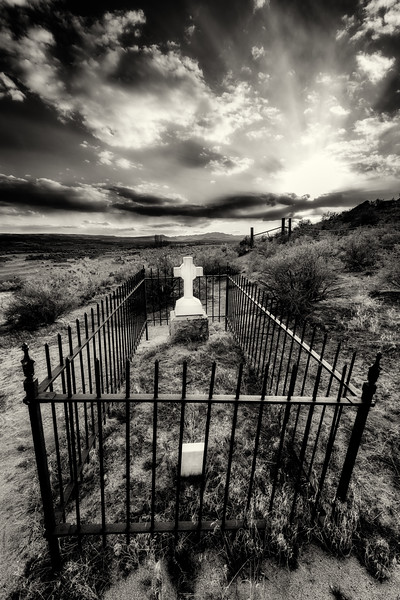 Rural cemetery in the desert during sunset with fence and tombstone