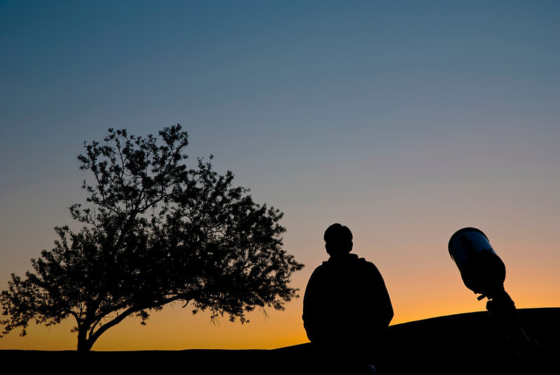 silhouette of an Astronomer and his telescope waiting for the sun to go down