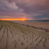 Sunrise over teh Atlantic ocean with fence and beach