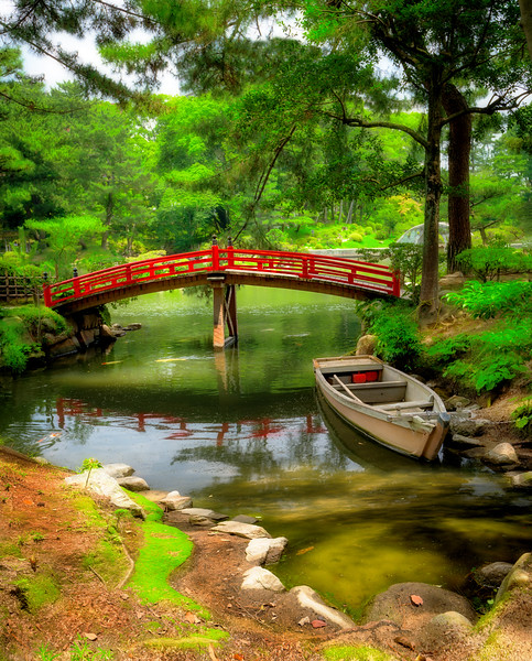 Peaceful boat on a pond with red bridge