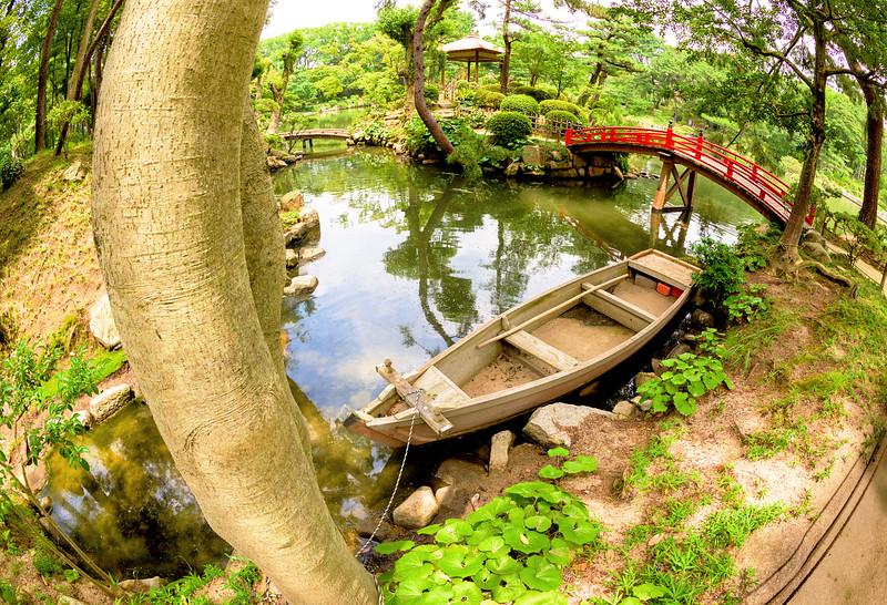 Red bridge and boat at SHUKKEIEN garden