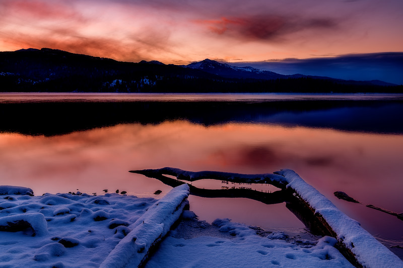 Icicles hang from a log sunrise over Little Payette Lake