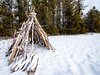 Handmade Tee Pee in winter with snow and a dark forest