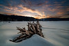 Winter snow drifts over Little Payette Lake in winter with sunrise painting clouds with color