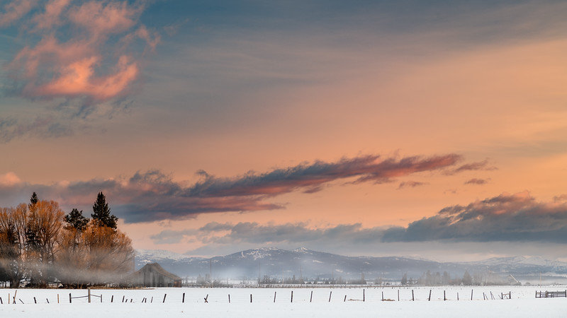 Farm near McCall fields covered with snow fogy sunrise
