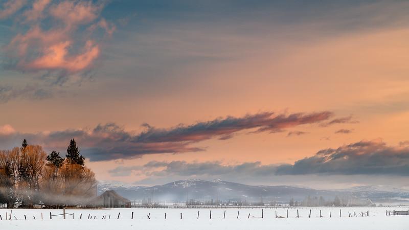 Farm near McCall fields covered with snow fogy sunrise