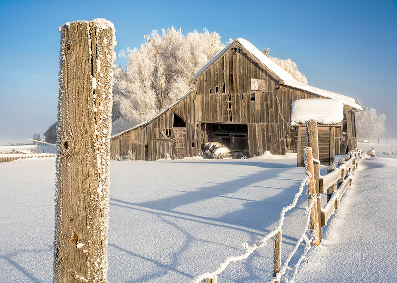 Close up of a fence post with wooden barn winter