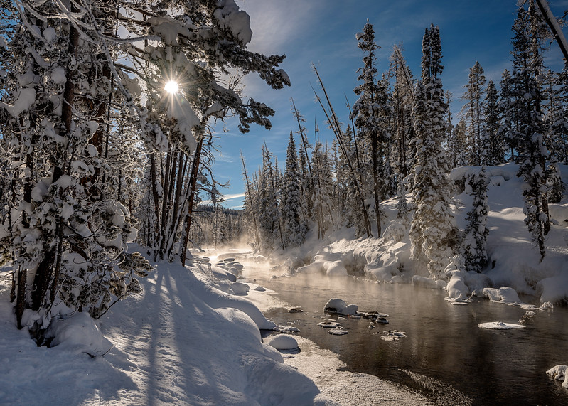 Winter creek with snow forest and sun star