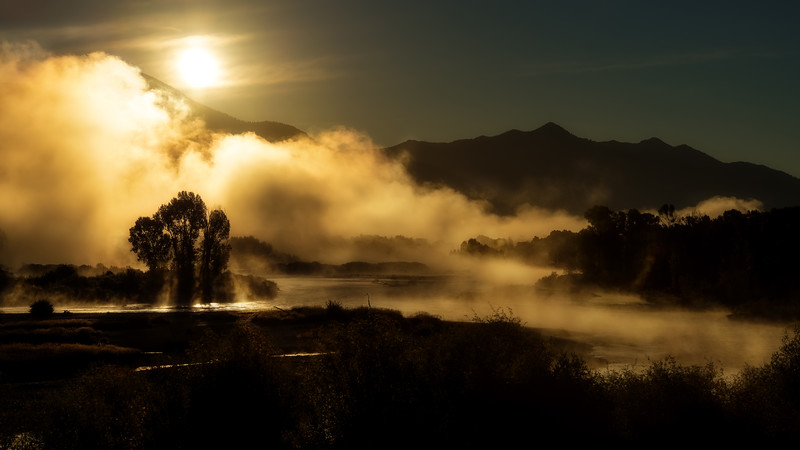 Fog lifts pver the Snake River as the sun rises in the sky
