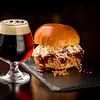 Pulled pork sandwich and a refreshing beer on a slate plate
