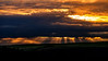 Sunrays shine through clouds as the sun sets over Eastern Washington farmland