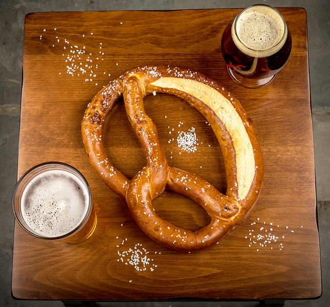 Two glasses of beer and an oversized pretzel with salt spilled