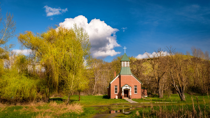Yellow willow and white clouds with Church reflection