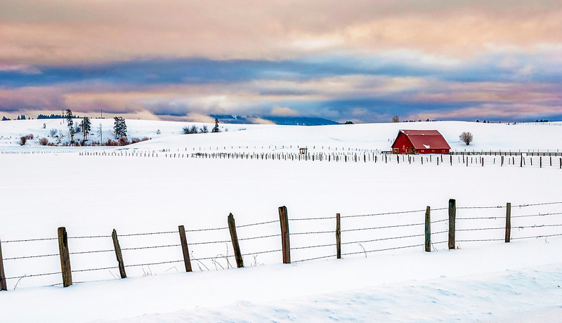 Red barn in a field of snow with a fence.