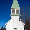 Small white country church located in Idaho with green roof and blue sky