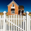 White picket fence gate boarders the land before a red brick house with dark sky