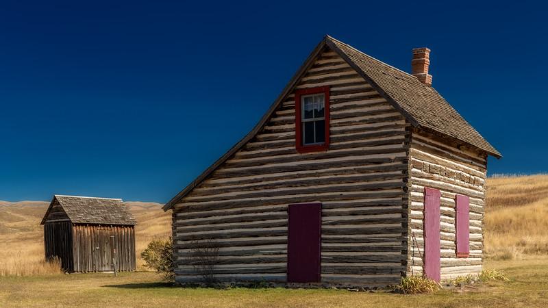Classic prairie home in rural Idaho farm land with blue sky
