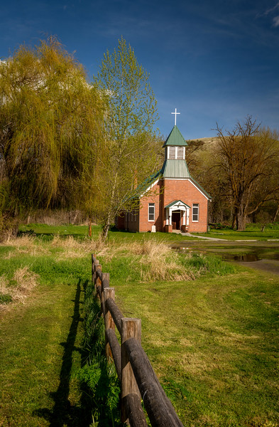 Wooden pole fence leads to a country church with willow tree and blue sky