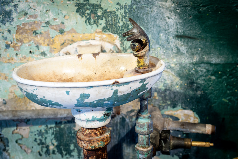 Very old water fountain with many layers of peeling paint