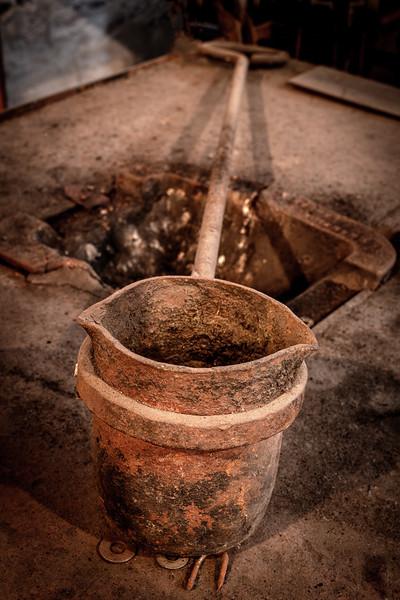 Molten metal pouring bucket in an ironsmith shop