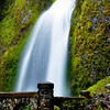 wahkeena falls with spring flow and a path leading to a foot bridge